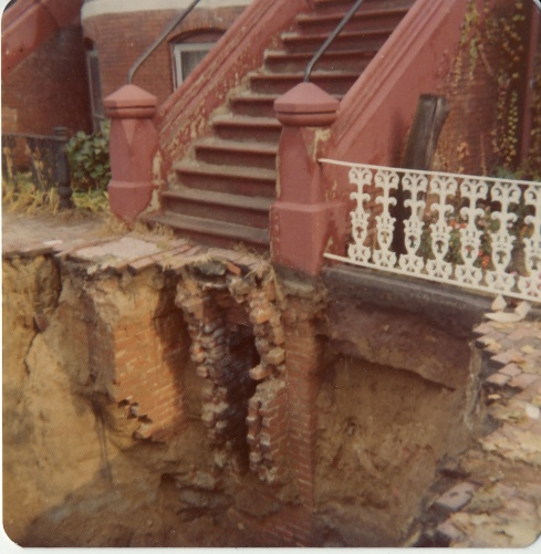 sidewalk opened showing brick foundation and coal chutes